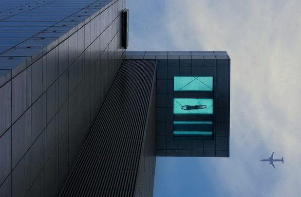 24th floor swimming pool with transparent bottom extends over side of Holiday Inn Hotel, Shanghai, China