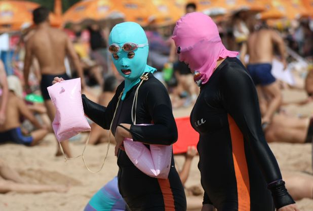 Women wear face masks and full body wetsuits for day at the beach