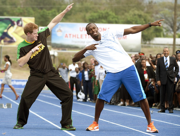 Prince Harry with Olympic sprint champion Usain Bolt doing his signature sign after a short sprint, at the University of the West Indies, in Jamaica where the Prince arrived late yesterday afternoon from The Bahamas.