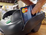 A customer swipes a MasterCard debit card through a machine