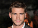 Liam Hemsworth refuses to answer paparazzi questions at the airport.
