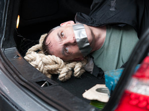 Mick is tied and gagged in the boot.