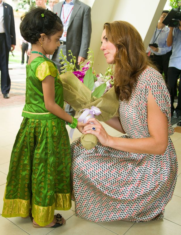 Duchess of Cambridge, eceives flowers from a young girl (name not known) during a visit to Queenstown in Singapore