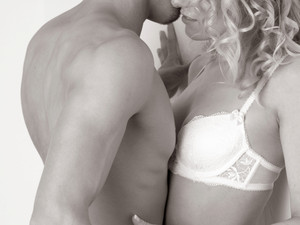 couple kissing against a wall. man and woman kissing. black and white. in underwear.
