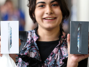 A customer holds two new iPhone 5's outside the Apple Store in Covent Garden