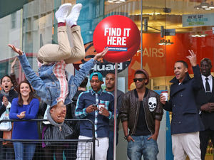 Aston Merrygold from JLS does a backflip to entertain crowds in the queue at a Carphone Warehouse store in London