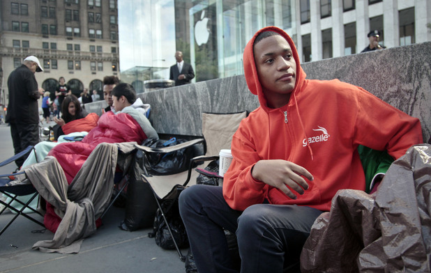 "Joseph Cruz, 19, far right, from Staten Island, N.Y., waits on line outside Apple's Fifth Avenue store on Thursday, Sept. 20, 2012, in New York. Cruz, who started camping last Friday to be one of the first to get the new iPhone 5, said ""it's unique, I just love the iphone."""