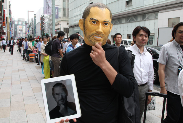 A customer wearing a mask of Steve Jobs
