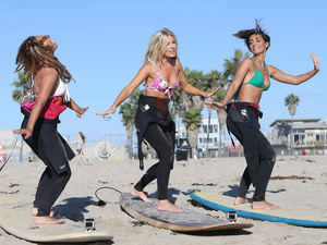 Vanessa White, Mollie King and Frankie Sandford of The Saturdays take surfing lessons on Venice Beach Los Angeles, California