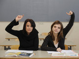Two school children in class with hands raised to answer a question for F in Retakes by Richard Benson