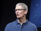 Apple CEO Tim Cook speaks talks in front of an image of an iMac and iPad