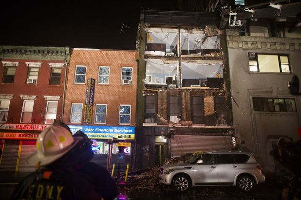 Firefighters look up at the facade of a four-story building on 14th Street and 8th Avenue that collapsed onto the sidewalk Monday, Oct. 29, 2012, in New York.