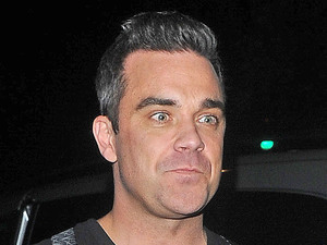 Robbie Williams leaves HMV in Oxford Street and heads for the Grosvenor House Hotel. London, England