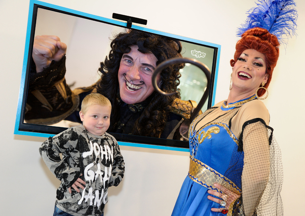 Craig Revel Horwood, dressed as the Wicked Queen from Snow White, visits Great Ormond Street Hospital. Paul Nicholas appears as Captain Hook on the TV screen.