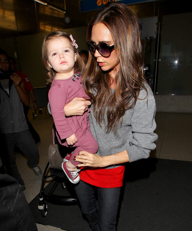 Victoria Beckham holds her daughter as the two arrive at LAX airport on a flight from London Heathrow.