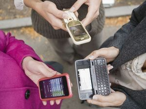 People sending text messages on mobile phones