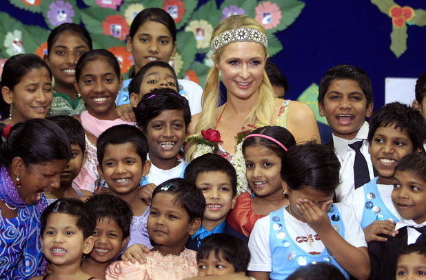 Paris Hilton, center, poses with children from Ashray, an orphanage, during her visit in Mumbai, India, Monday, Dec. 3, 2012.