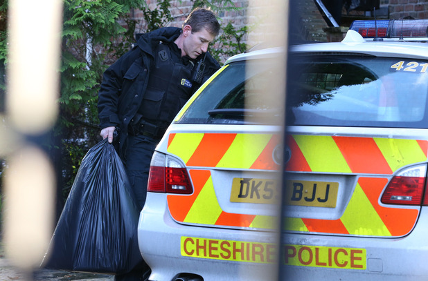 A police officer carrying a plastic bags from the home of Stuart Hall in Wilmslow, Cheshire following the arrest of the veteran BBC commentator over allegation of rape and indecent assault.