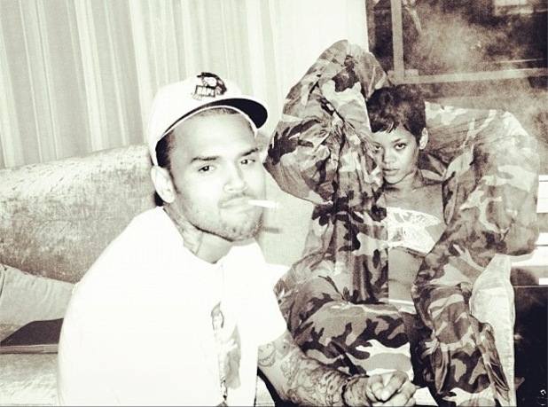 Rihanna and Chris Brown sit together in black and white image