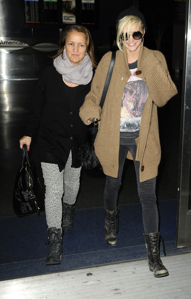 Ashlee Simpson wearing an oversized cardigan arrives at JFK airport with her mother, Tina
