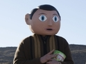 Prometheus star dons a giant Frank Sidebottom head for his new comedy.