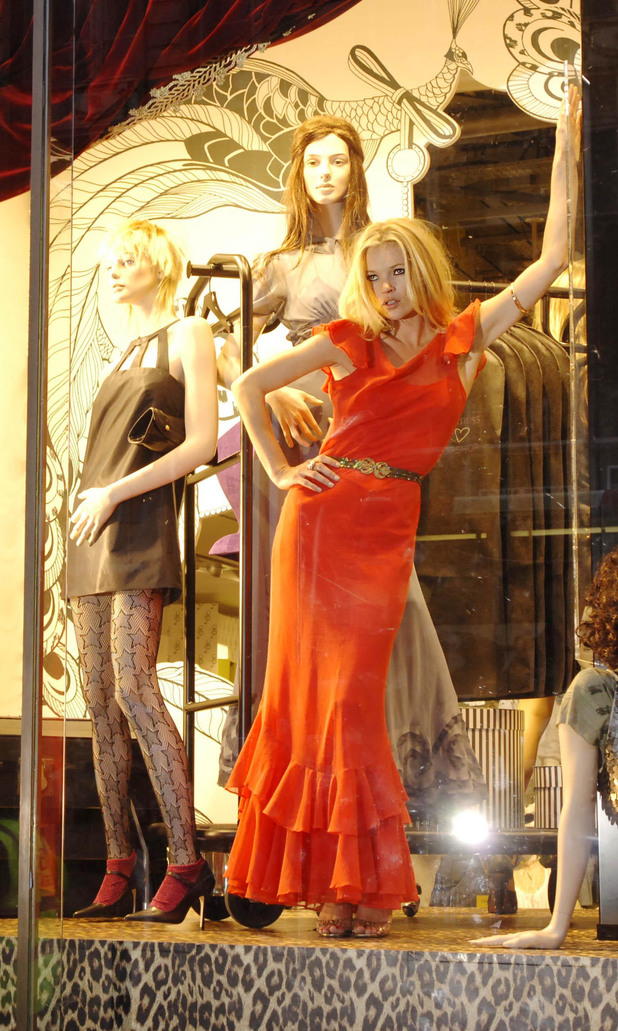 Supermodel Kate Moss poses in the window of the Topshop store in Oxford Street, central London, to launch her first collection for the store