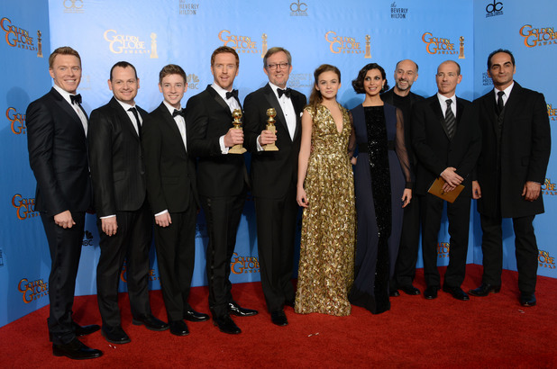"Damian Lewis, center left, producer Alex Gansa, center right, and the cast and crew pose with the award for for best television series drama for ""Homeland"" backstage at the 70th Annual Golden Globe Awards"