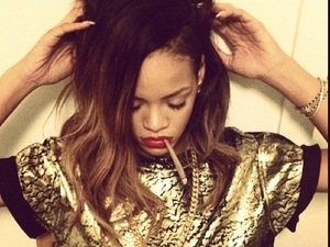 Rihanna poses with a roll-up in a gold T-shirt while at rehearsals for her Diamonds world tour