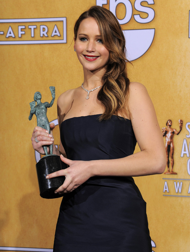 "Jennifer Lawrence poses backstage with the award for best female actor in a leading role for ""Silver Linings Playbook"" in the press room at the 19th Annual Screen Actors Guild (SAG) Awards"