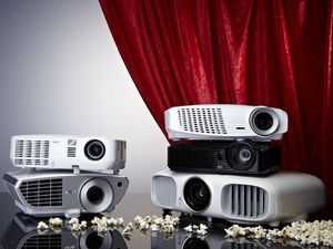 A Selection Of Projectors Photographed In Front Of A Cinema-style Curtain And Popcorn