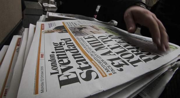 A man collects a free copy of the Evening Standard daily newspaper