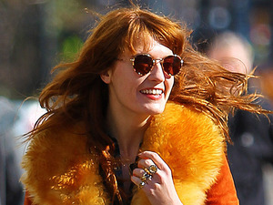 Florence Welch wears an orange winter coat with a large fur collar while out for an afternoon walk