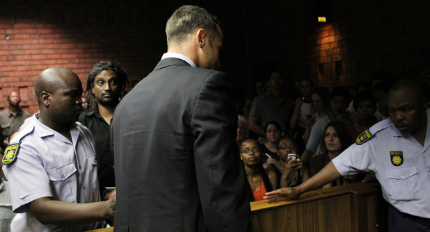 Oscar Pistorius is lead out of the witness bench after his bail application appearance in Pretoria
