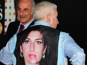 Mitch Winehouse arrives wearing a waistcoat bearing a picture of his daughter Amy at the 2013 Brit Awards