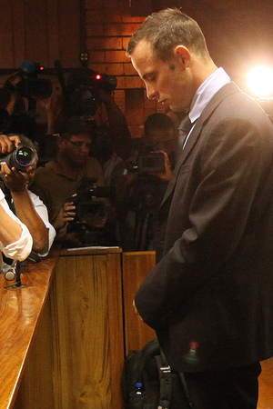 Photographers take photos of Oscar Pistorius as he stands in the dock during his bail hearing