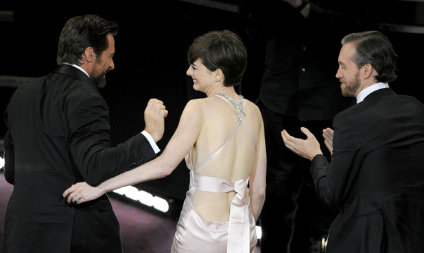 Anne Hathaway is congratulated on her Oscar win by co-star Hugh Jackman and her husband Adam Shulman