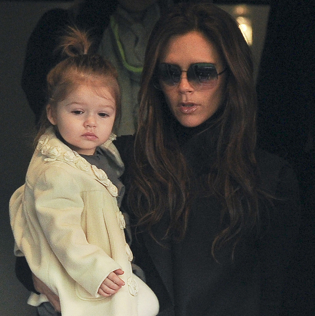 Victoria Beckham and daughter Harper watch David Beckham play a match.
