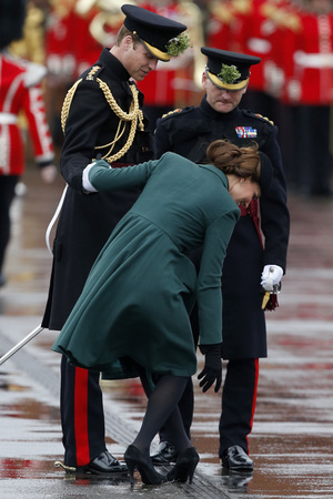 Kate Duchess of Cambridge bends down to pull the heel of her shoe out of a drainage grill after it got stuck.
