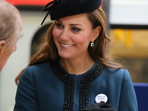 Kate Middleton wears a 'Baby On Board' badge during her visit to Baker Street tube station