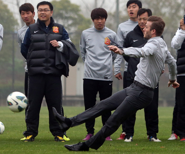 David Beckham slips over during a visit to Zall Football Club.