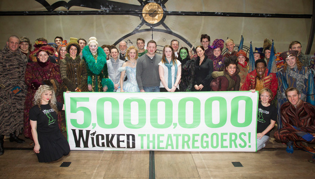 Members of the cast pose with the five millionth customers, Stewart Lyons and Cristina Kane, after the curtain call for Wicked at the Apollo Victoria Theatre,