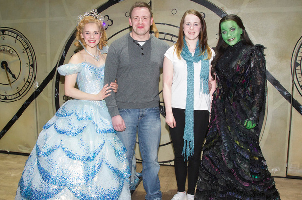 Gina Beck (Glinda) and Louise Dearman (Elphaba) backstage with the five millionth customers, Stewart Lyons and Cristina Kane, after the curtain call for Wicked at the Apollo Victoria Theatre,