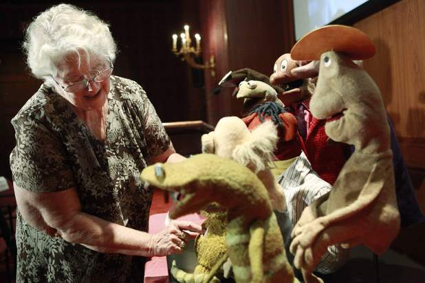 Jane Henson photographed at the Smithsonian Institute in 2010, arranging some of Jim Henson's early puppets including the original Kermit