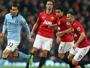 Manchester United's Ryan Giggs, Rafael and Rio Ferdinand, from right, pursue Manchester City's Carlos Tevez, left, during their English Premier League soccer match at Old Trafford Stadium, Manchester, England, Monday April 8, 2013