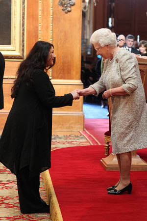 Kate Bush receives her CBE from Queen Elizabeth II during an Investiture ceremony at Windsor Castle