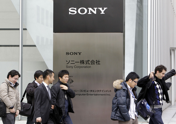 Office workers leave the headquaters of Sony Corp. in Tokyo