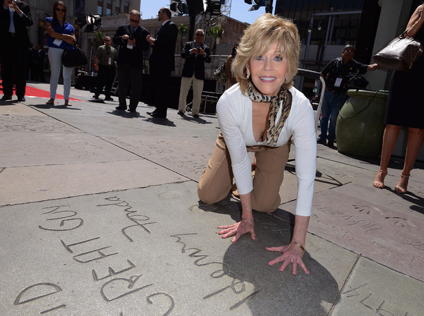 Jane Fonda compares her hands with her father, Henry Fonda's hand and footprint.
