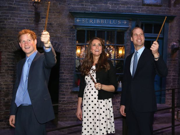 Prince Harry, the Duchess and Duke of Cambridge raise their wands on the set used to depict Diagon Alley in the Harry Potter Films during their visit to Warner Bros studios in Leavesden.