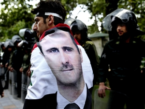 An Syrian man wrapped in a Syrian flag with a portrait of President Bashar Assad