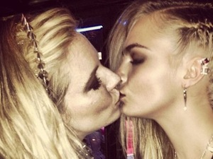 Cara Delevingne kisses Sienna Miller at the Met Ball.